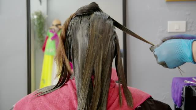 asiatische professionelle haarfärbemittel, sie färbt das haar für die kunden. ist ein kleines unternehmen. - haartönung stock-videos und b-roll-filmmaterial