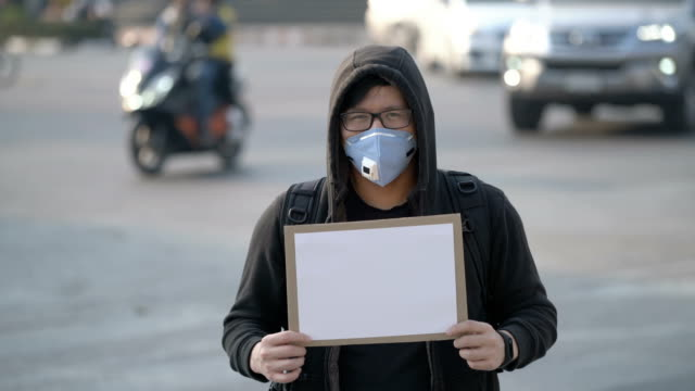 Asian Protest Man holding White borad with pollution mask in traffic