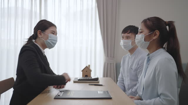 Asian Real estate agent woman give keys to customer after signing contract to buy house, insurance or loan real estate while wearing masks to prevent the spread of COVID-19. Asian Real estate agent woman give keys to customer after signing contract to buy house, insurance or loan real estate while wearing masks to prevent the spread of COVID-19. mortgages and loans stock videos & royalty-free footage