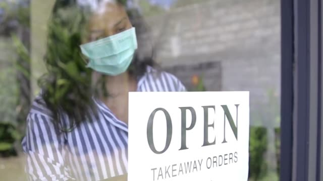 Asian restaurant owner hanging an open sign for takeaway order into the window