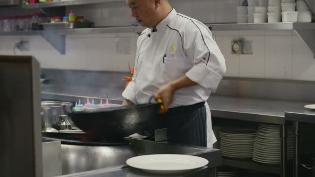 asian restaurant, professional chef cooking food, man, chinese cook working - kinesisk kultur bildbanksvideor och videomaterial från bakom kulisserna