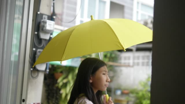 Asian schoolgirl using yellow umbrella in raining day, lifestyle cocnept.