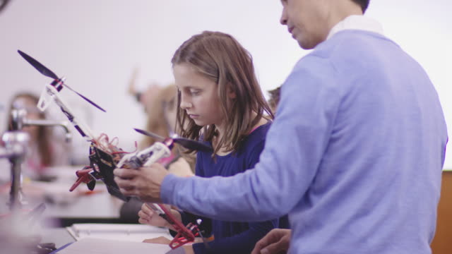 Asian Science Teacher Examining a Drone with an Elementary-Age Student An elementary student examines a drone her teacher hands her stem topic stock videos & royalty-free footage