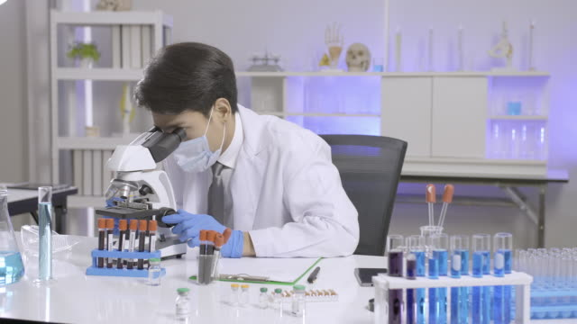 Asian scientist doing some research and looking through a microscope in laboratory. video