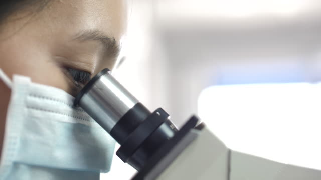 Asian scientist looking through a microscope in a laboratory