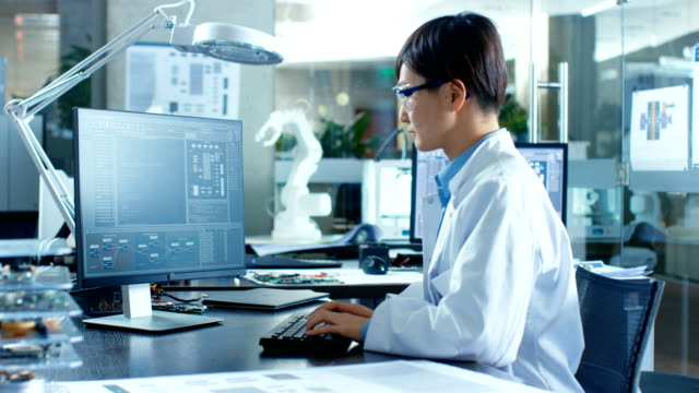 asian scientist sitting at his desk doing sophisticated coding and programming on his desktop computer. in the background computer science research laboratory with robotic arm model. - электронная промышленность стоковые видео и кадры b-roll