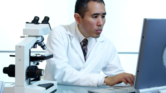 Asian scientist uses microscope and computer video