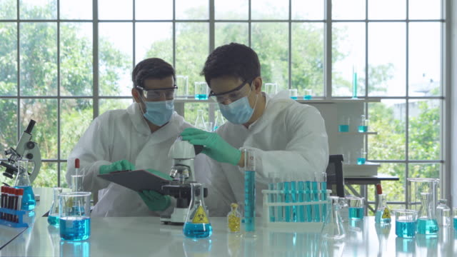asian scientist working on blue test tube to analysis and develop vaccine of covid-19 virus in lab or laboratory in technology medical, chemistry, healthcare, research concept. experimental science - {{relatedsearchurl(carousel.phrase)}} video stock e b–roll