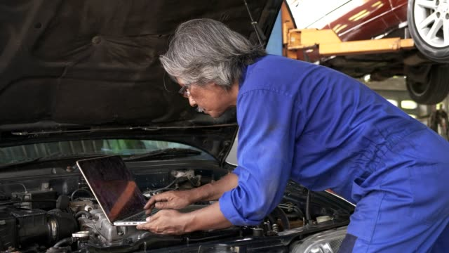 Asian senior auto mechanic check condition of engine and electric system ,record on the list.check engine oil level,check electric fuse.Used computor diagnosis damage of engine.