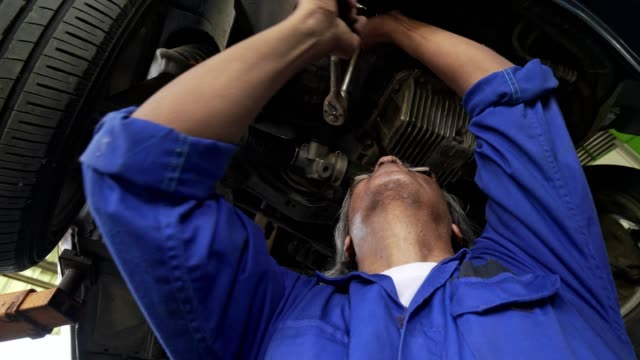 Asian senior auto mechanic check condition of engine and electric system ,record on the list.check engine oil level,check electric fuse.Checking oil leak and suspension underneat car.