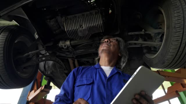 Asian senior auto mechanic check condition of engine and electric system ,record on the list.check engine oil level,check electric fuse.Checking oil leak and suspension underneat car.Used tablet record and checking damage of suspension.