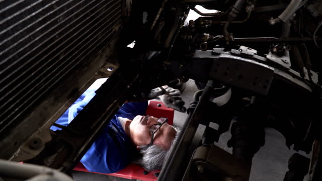 asian senior car mechanic move yourself to work under vehicle - sotto video stock e b–roll