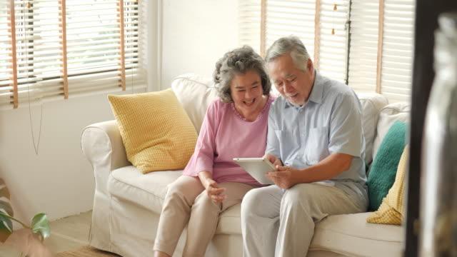 アジア シニア カップルがデジタル タブレットを使用して、話していると、自宅でソファに座って笑顔します。技術コンセプトを持つ人々。 - シニア点の映像素材/bロール