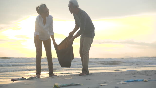 Asian senior couple cleaning up the beach with plastic bags full of garbage. Slow Motion. Safe ecology concept. 4k resolution.