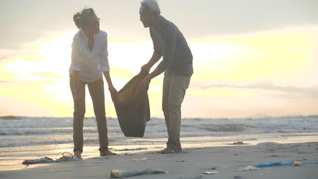 asiatiska senior par städa upp på stranden med plastpåsar full av sopor. slow motion. säkert ekologi koncept. 4k-upplösning. - välgörenhet bildbanksvideor och videomaterial från bakom kulisserna