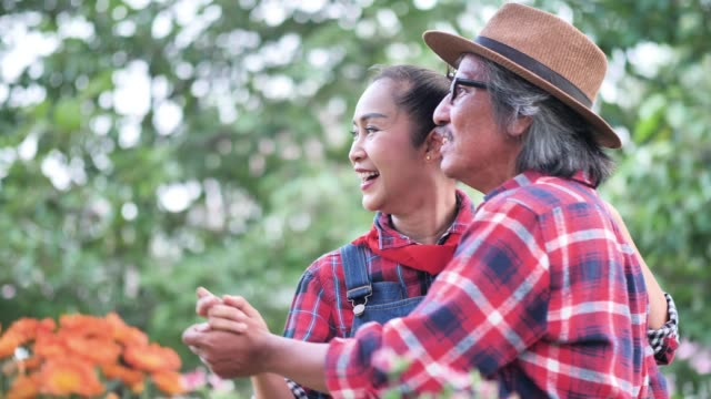vídeos de stock e filmes b-roll de asian senior couple dancing together in garden at home. family, happy, health, environment, hobbies after retirement.  slow motion - 55 59 anos