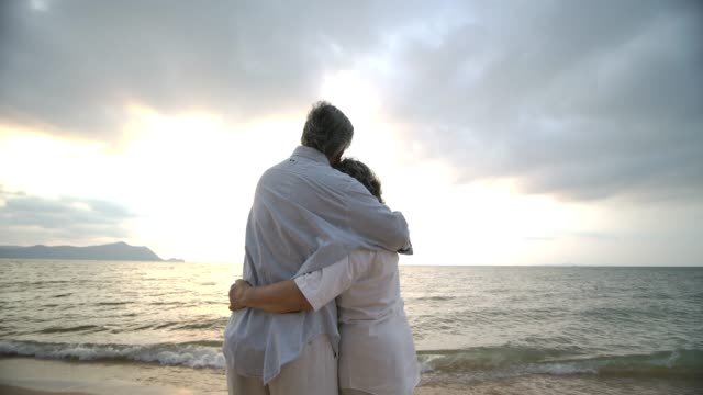 asian senior couple embracing each other on the beach in slow motion. - love video stock e b–roll
