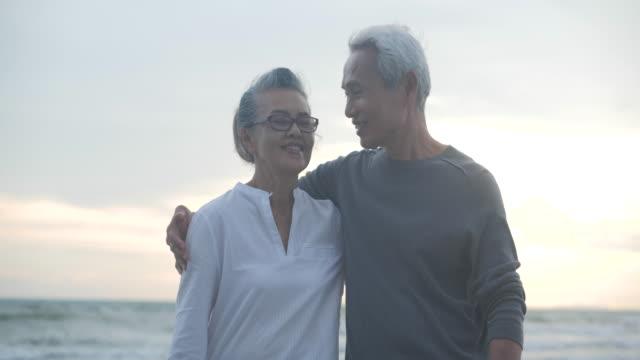 asiatische senior-paar umarmt sich am strand in zeitlupe. - seniorenpaar stock-videos und b-roll-filmmaterial