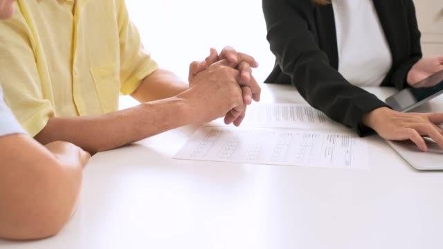 vidéos et rushes de asiatique couple aîné obtenir des conseils de planificateur financier à la maison. vieillissement à la maison. - expliquer