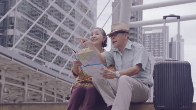 vidéos et rushes de couples asiatiques de aîné retenant la carte à la recherche des rues de destinations en thaïlande, après l'âge de la retraite des personnes âgées voyageant avec leurs propres économies, voyageurs et mode de vie de concept plus ancien - couple marié