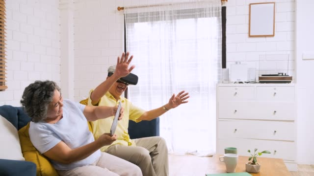 Asian senior couple play virtual realtiy glasses headset and tablet watching vr video and  have fun together on sofa  in living room at home.senior with technology.aging at home.