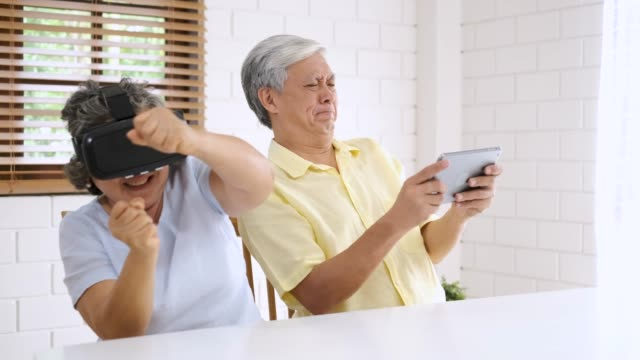 Asian senior couple play virtual realtiy glasses headset and tablet watching vr video and  have fun together in living room at home.senior with technology.aging at home.