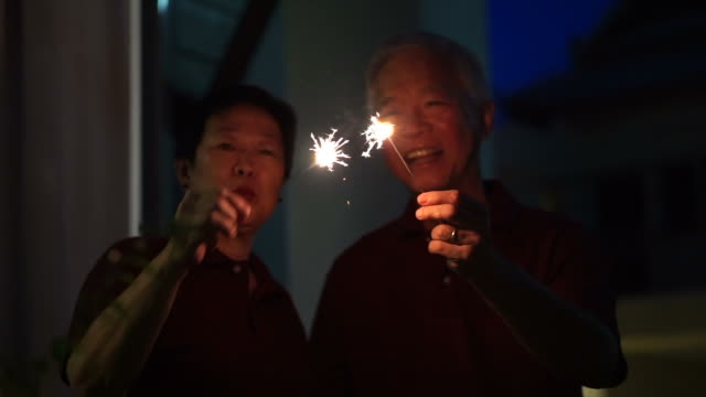Asian senior couple playing firework, sparklers, fire cracker at night. Concept celebrating life video