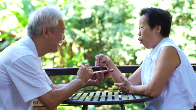 Asian senior couple playing game together on smart phone having fun winning in park video