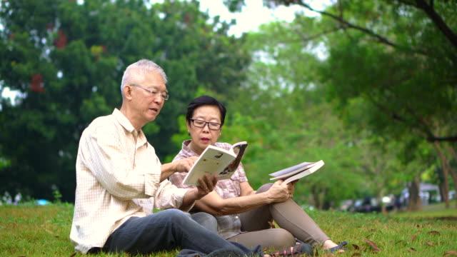 アジア シニア カップル公園で本を読みます。充実した時間を過ごすし、何か新しい学習を停止すること - 老夫婦点の映像素材/bロール