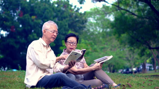 Asian senior couple reading books at the park.Spend quality time and never stop learning something new video