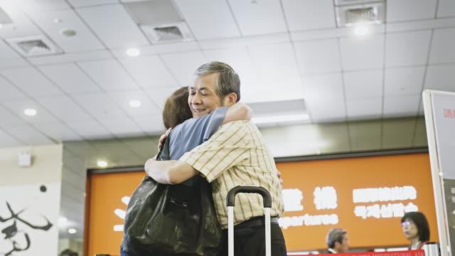 空港でさよならを言うアジアのシニアカップル - 乗客点の映像素材/bロール