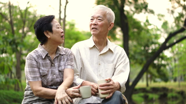 Asian senior couple showing affectionate and care through a cup of coffee in morning bright natural park video