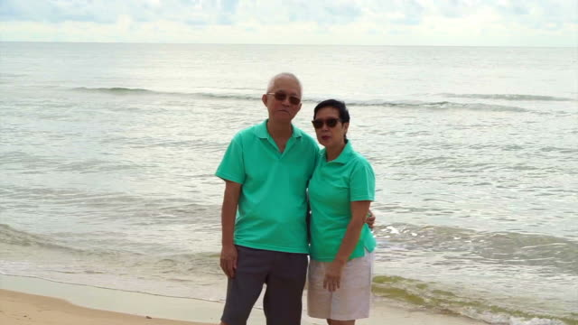 Asian senior couple stand at the beach at looking to ocean video