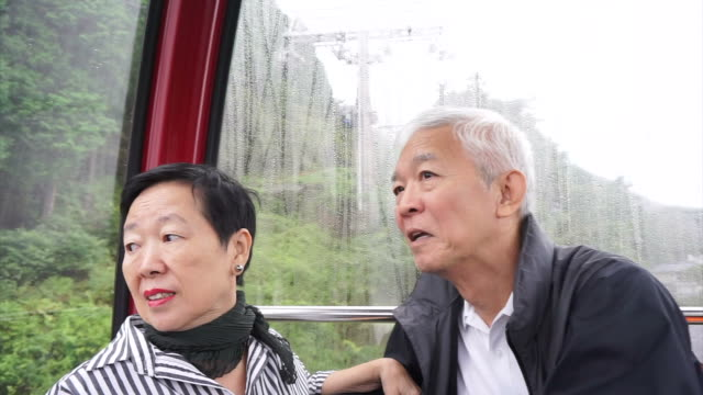 Asian senior couple traveling on ropeway cable car up in the mountain for retirement trip video