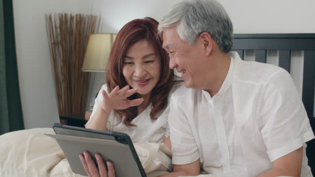 Asian senior couple using tablet at home. Asian Senior Chinese grandparents, video call talking with family grandchild kids while lying on bed in bedroom at home in the morning concept. Slow motion.