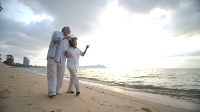 アジアのシニア カップル ウォーキングや美しい熱帯のビーチでスローモーションで話しています。 - 老夫婦点の映像素材/bロール
