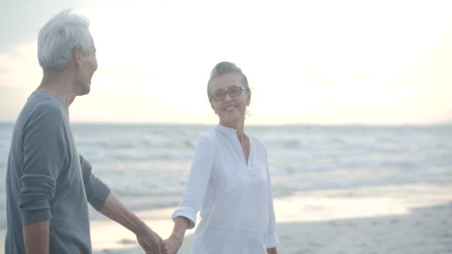 asian senior couple walking and talking on beautiful tropical beach in slow motion. - sud est asiatico video stock e b–roll