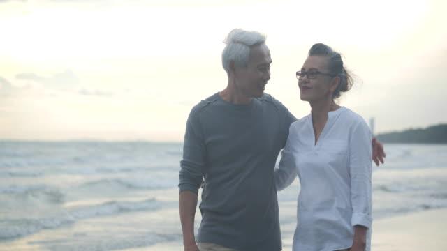 アジアのシニアカップルがスローモーションで美しい熱帯のビーチを歩き、話しています。 - 老夫婦点の映像素材/bロール