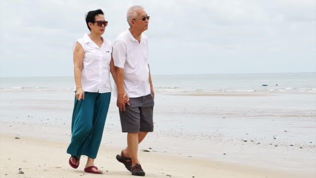 Asian senior couple walking happily by the beach. Well plan retired lifestyle no financial problem video