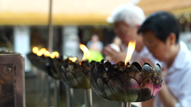 Asian senior doing Buddhist ritual pouring oil to fill candle flame for Buddha statue video