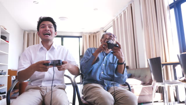 Asian senior father and his adult son enjoy playing video games together in living room at home