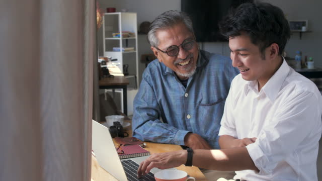 Asian senior father and his adult son using laptop computer while sitting at home