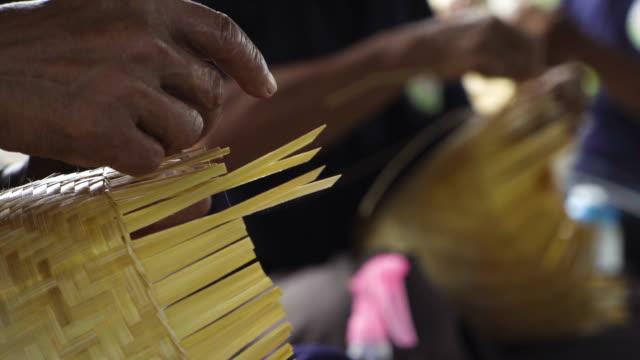 asiatiska senior hand hantverk att göra, händer vävning bambu korg, koncept: handgjorda, traditionella. - halmslöjd bildbanksvideor och videomaterial från bakom kulisserna