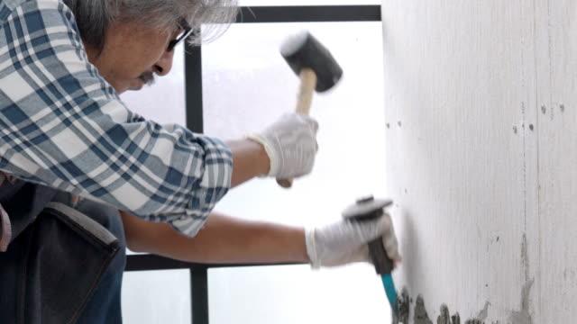 vídeos de stock, filmes e b-roll de 4k faz-tudo sênior asiático usando cinzel e martelo descascando azulejo de parede cerâmica. técnico sênior reparar obras de construção ou reforma da casa. velho sênior diy conceito de trabalho. - descascado