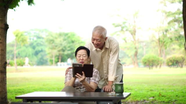 デジタル通信用パッドの使用を笑ってアジア シニア - タブレット端末点の映像素材/bロール