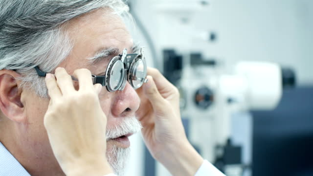 Asian senior male patient having him eyes examined by an eye. Optometrist taking eye test through trial frames at the clinic. Doctoroptometry concept. 4k resolution. video