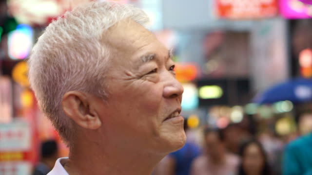 Asian senior man enjoying travel trip at evening out in Mongkok, Hong Kong video