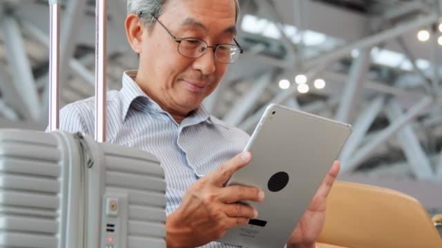 アジアの先輩男性は、彼の研究室の画面を見て、微笑んでいます。彼は空港に座っている。旅行、旅、グローバル、ライフスタイル、休日、技術の概念。空港内 - 乗客点の映像素材/bロール
