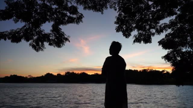 asiatisk senior man silhuett i gryningen under träd skugga. att tänka på livet - abstract silhouette art bildbanksvideor och videomaterial från bakom kulisserna