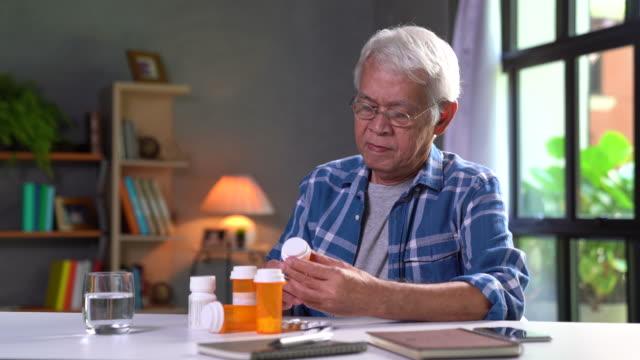 asiatisk senior man tar medicin - pillerflaska bildbanksvideor och videomaterial från bakom kulisserna